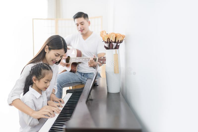 asian family mother daughter playing piano father playing asian family mother daughter playing piano father playing guitar 101001183