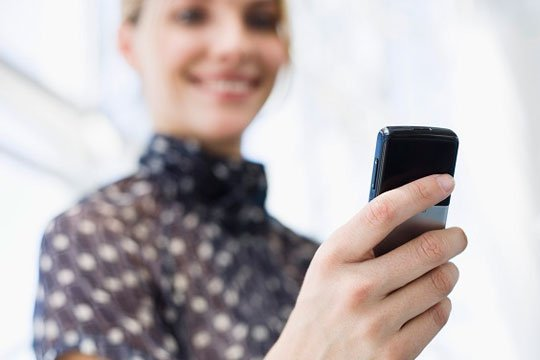 woman holding mobile phone main